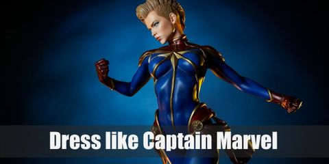 Captain Marvel's outfit is a full-body uniform with red and blue pattern that has the Kree symbol on the chest. She also wears red gloves, red boots, and a red belt.