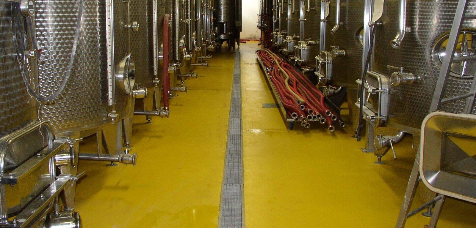 Autoclavi per la produzione del vino poggiate su di una pavimentazione in resina ad uso alimentare in una cantina.