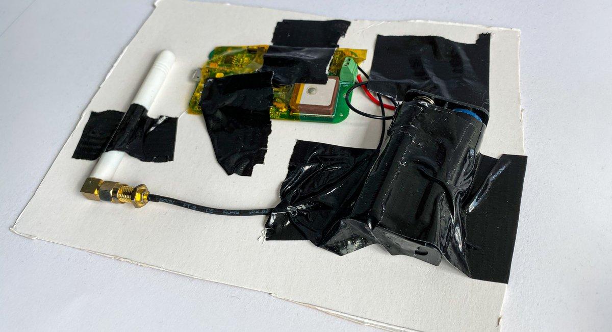 GPS-Tracker, Batterie-Halterung und Antenne mit abgerupftem Gaffertape auf eine schief ausgeschnittene Pappe geklebt