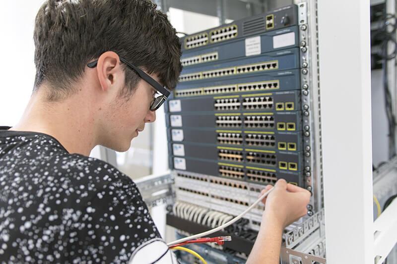 Žák napojuje kabely do počítačového serveru