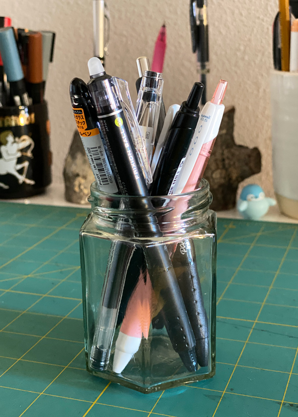 A cup of pens on a desk, with more pens in the background