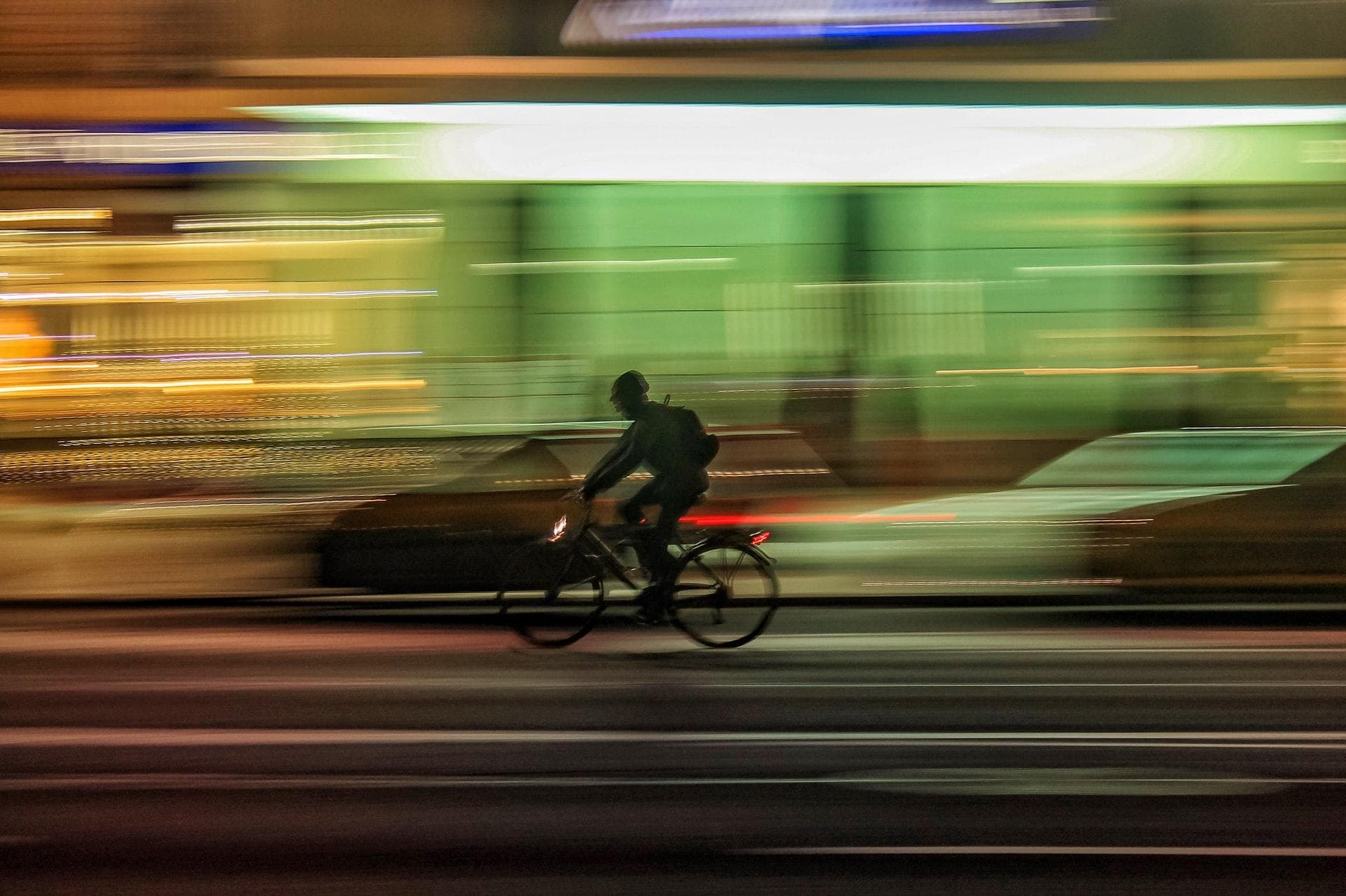 A fast biker. Background are city lights at night, blurred due to the high speed of biker