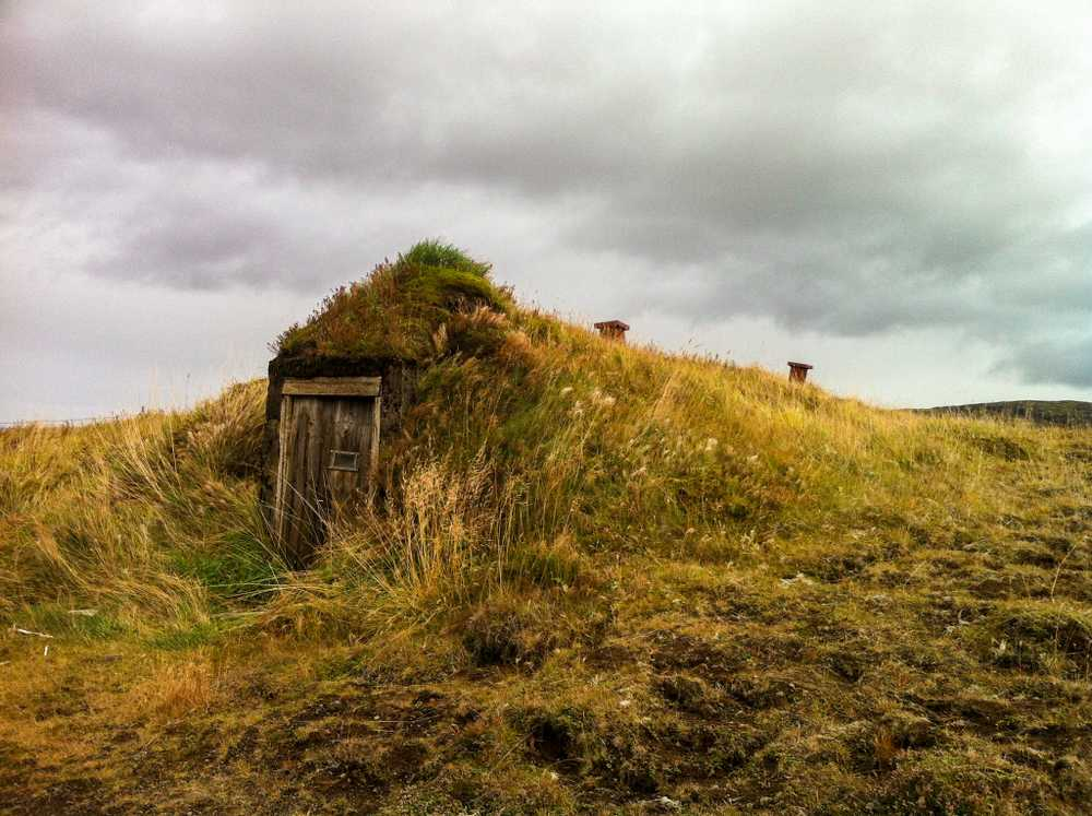 An old-fashioned turf building, barely visible