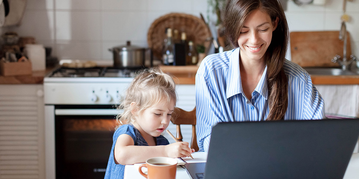 A woman sitting at a desk in front of a laptop with a child drawing
