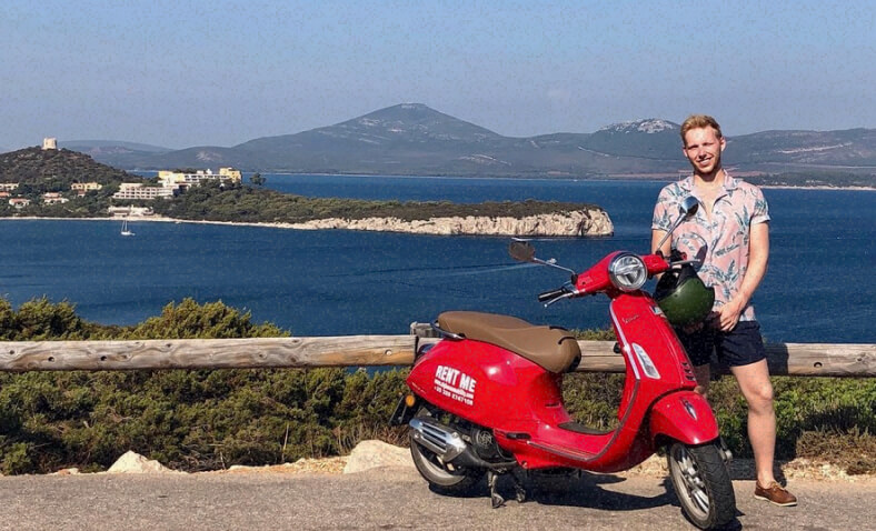 Frederick standing between a red Vespa and the beautiful Italian landscape.