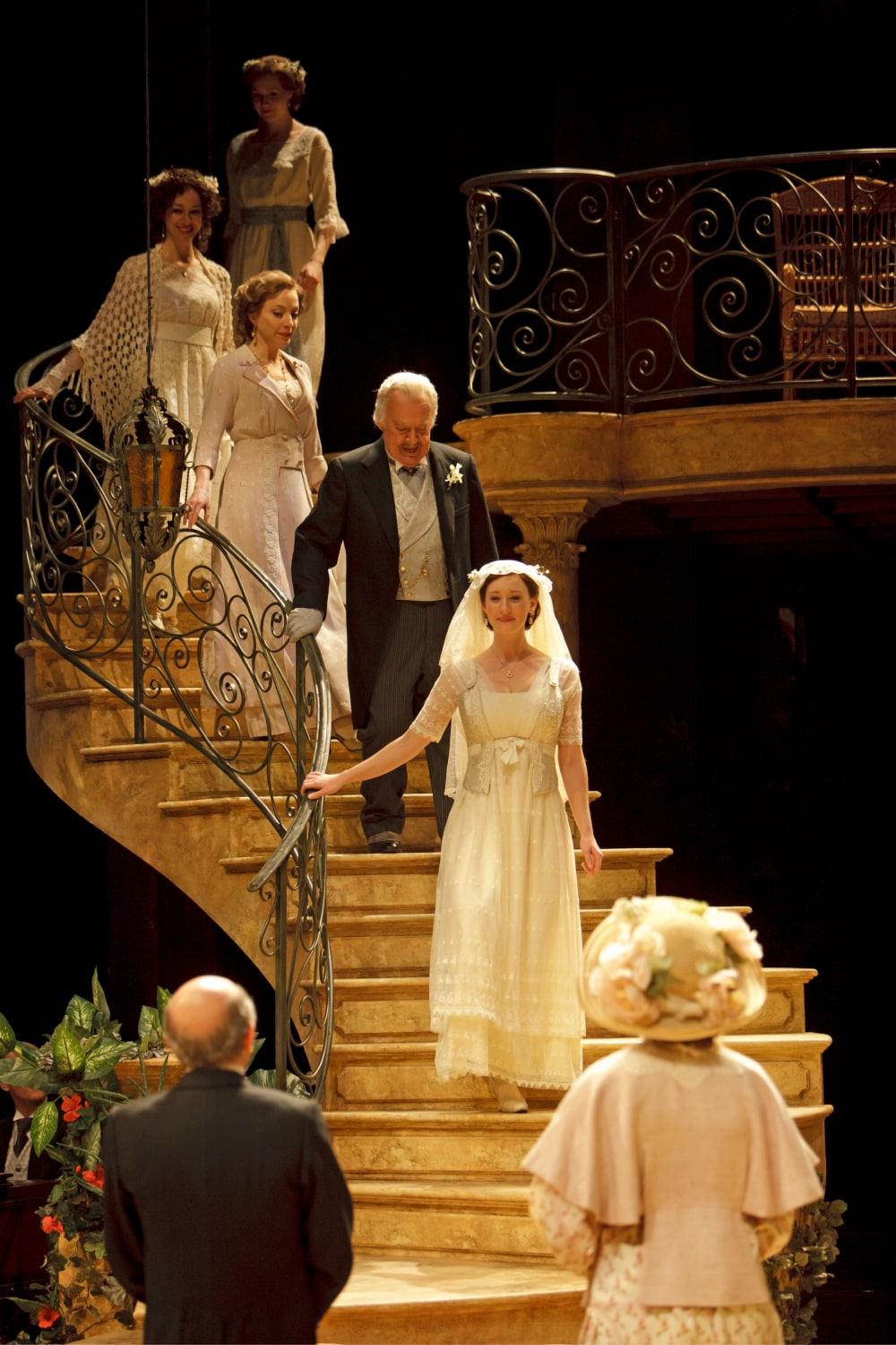 Bridal party descends curved staircase in warm light.