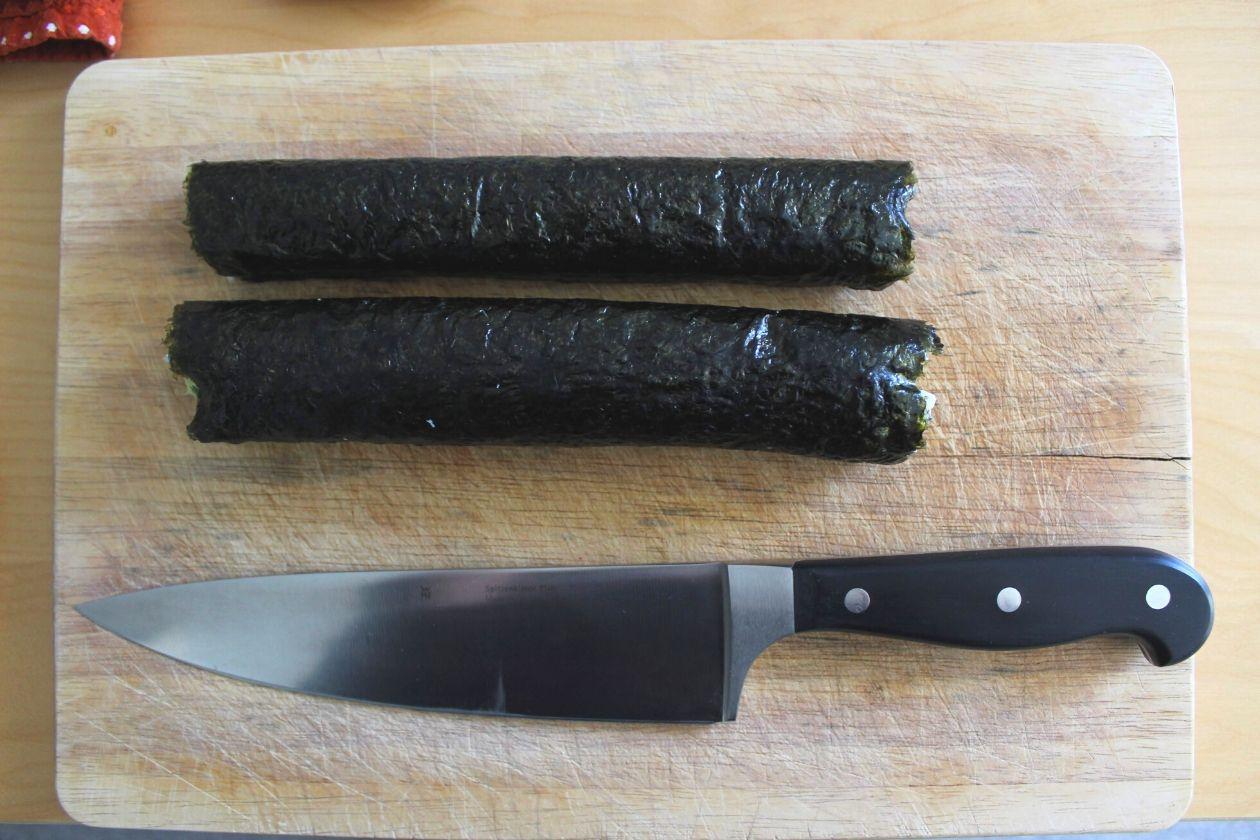 Die fertigen Sushi-Rollen auf einem Brett. Darunter liegt ein Messer.