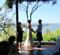 Photo of Janne holding a microphone for the bride who is saying her vows, the background is of the Swan River in Perth with part of Kings Park in the distance. The groom is also in the shot and is listening to the bride.