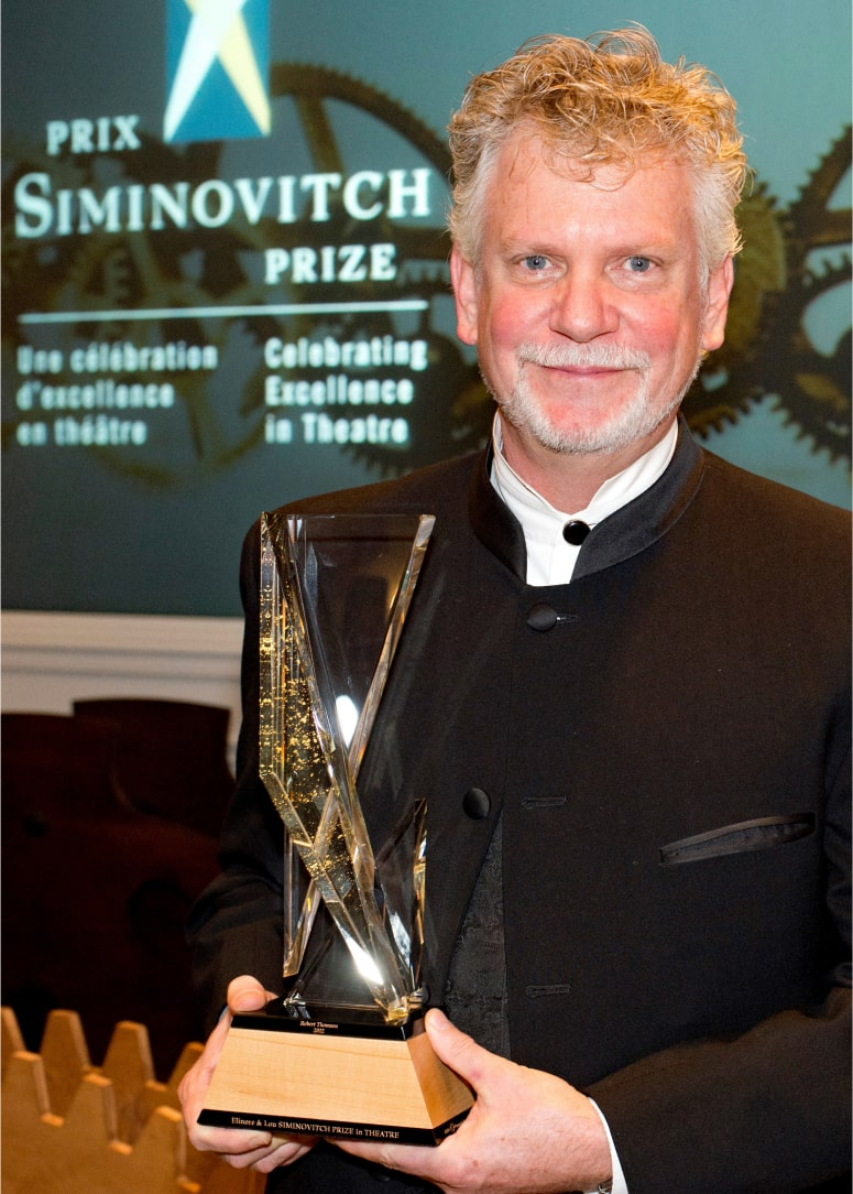 """Robert Thomson, holding crystal award statue, in front of wall sign """"Prix Siminovitch Prize""""."""