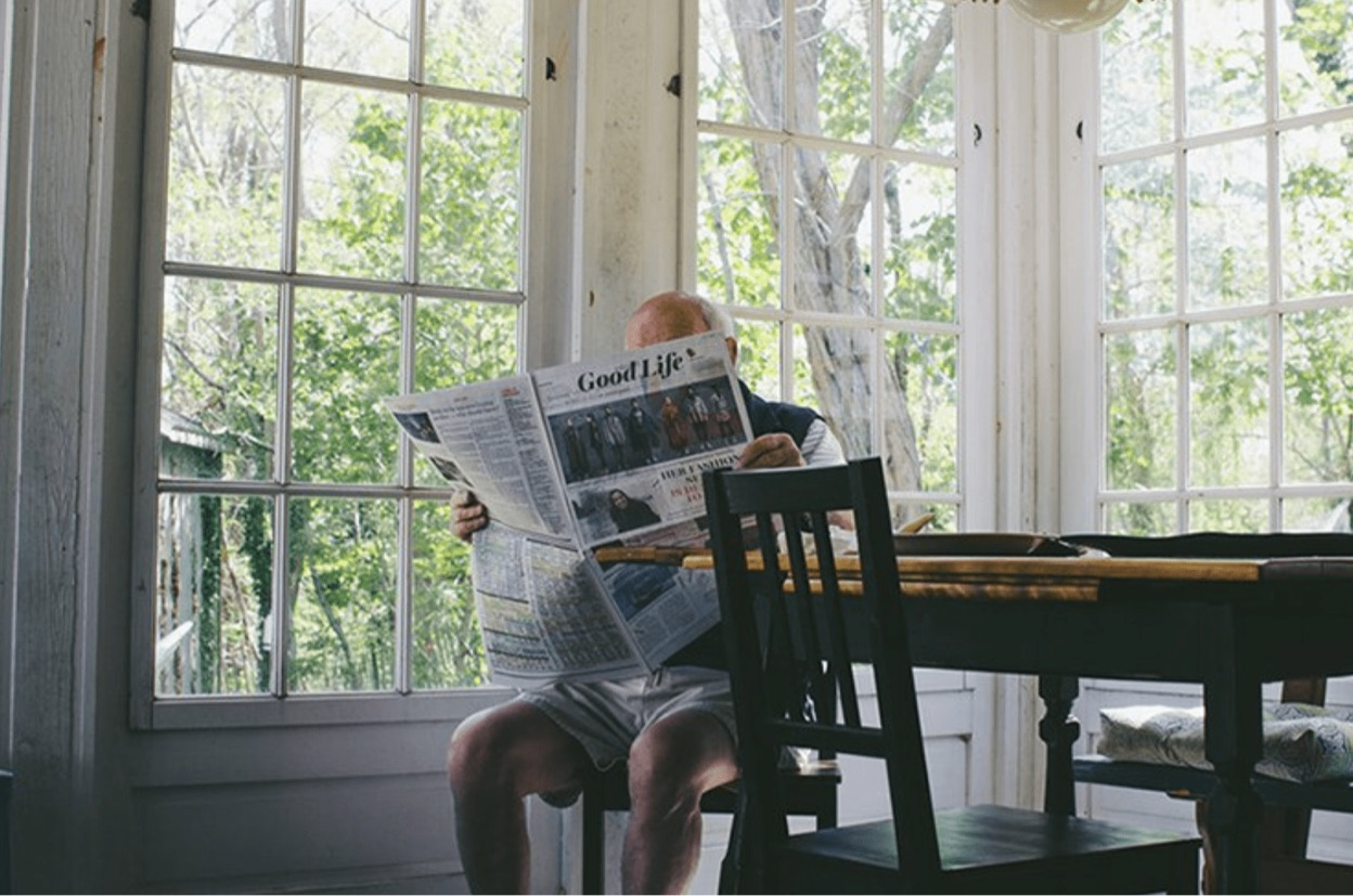 An elderly man, sitting at a dining table, reading a newspaper.