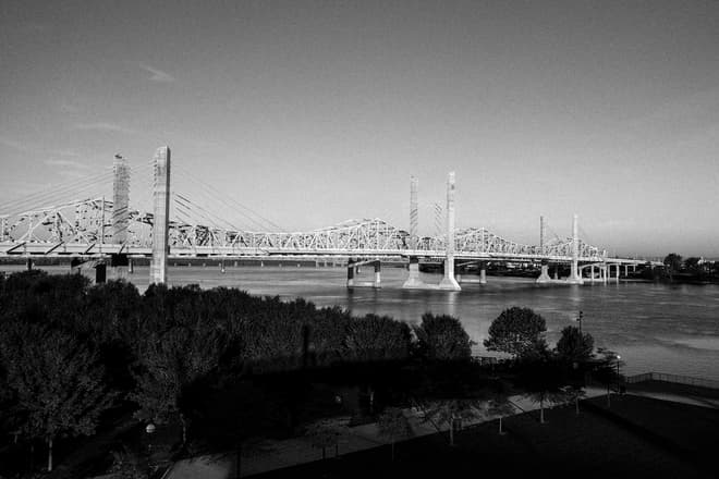 A black-and-white photograph of a brutalist suspension bridge of white steel and concrete pylons crossing the Ohio River.