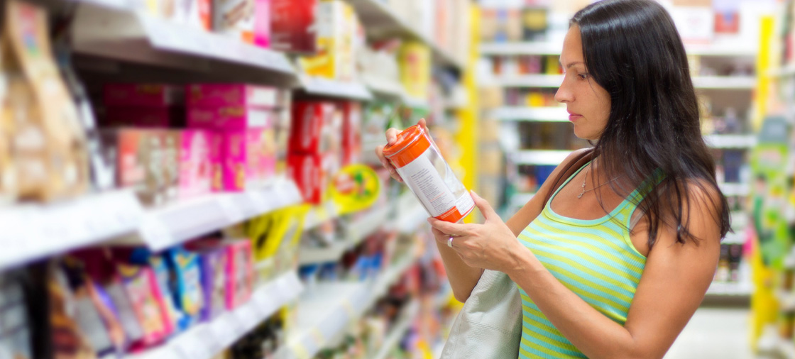 Woman reading a product label in a grocery store