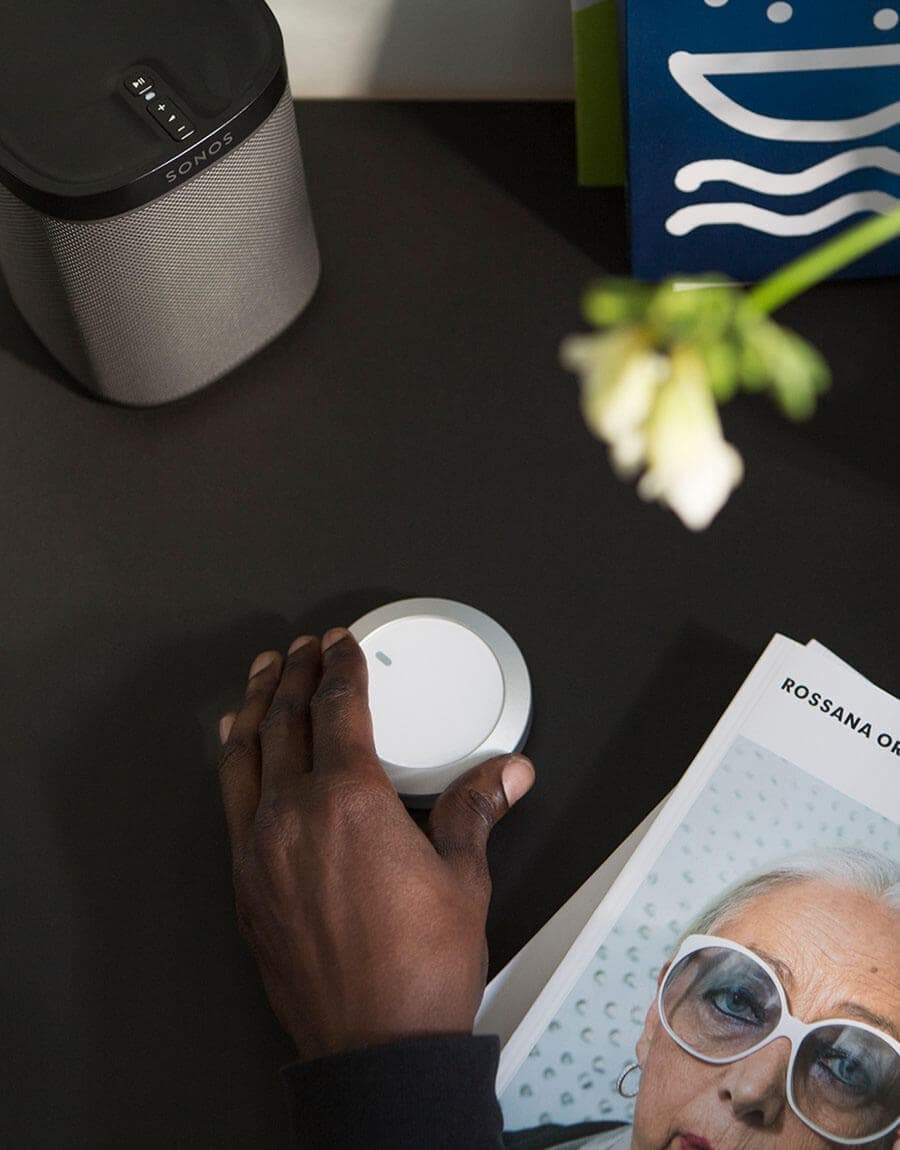Nuimo control white being used by an afro-american user next to a Sonos speaker and some documents