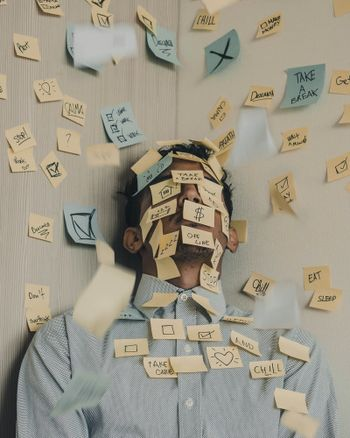 Sticky notes all over a tired person's face