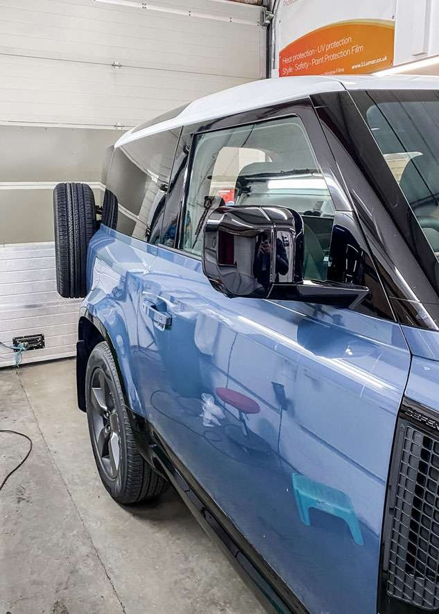 Blue Land Rover Defender with vinyl wrapped white roof