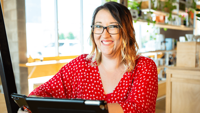 Katherine Haines, a bookkeeper and advisor at her own firm KHB Darwin, facing the camera while using an iPad tablet, wearing a red top, black glasses and sitting in from of a window.