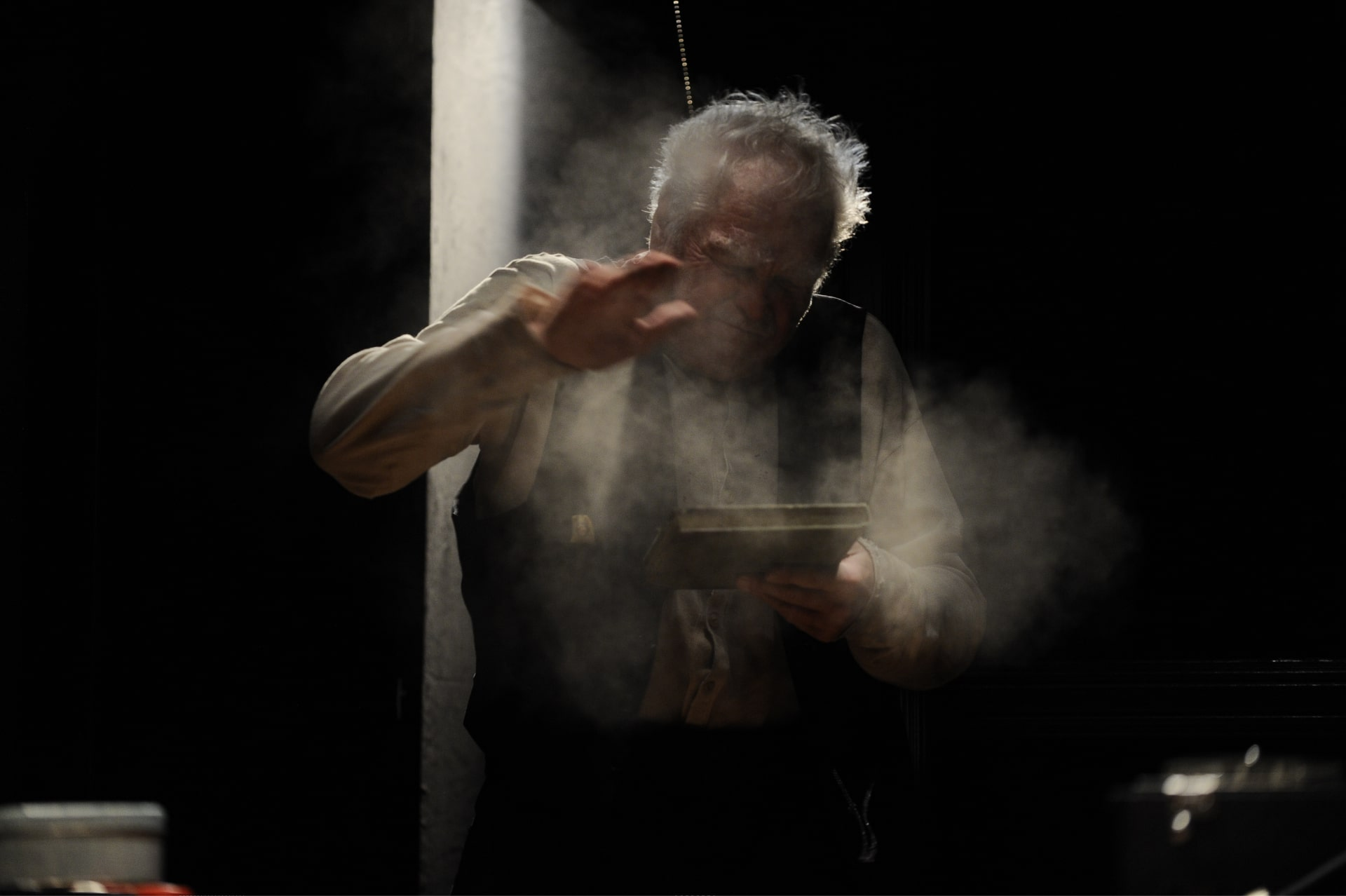 Older man in waistcoat thumps dust from book in front of strong shaft of light.