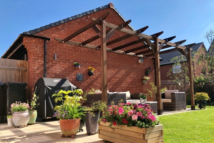 An example of module 2, built against a brick house, and surrounded by a barbeque, wicker furniture, and potted flowers