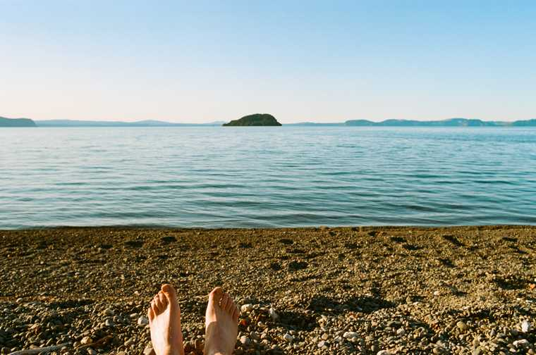 My bare feet enter the bottom of the frame of a photo looking out on blue Lake Taupo from the rocky shore a couple hours before sunset.
