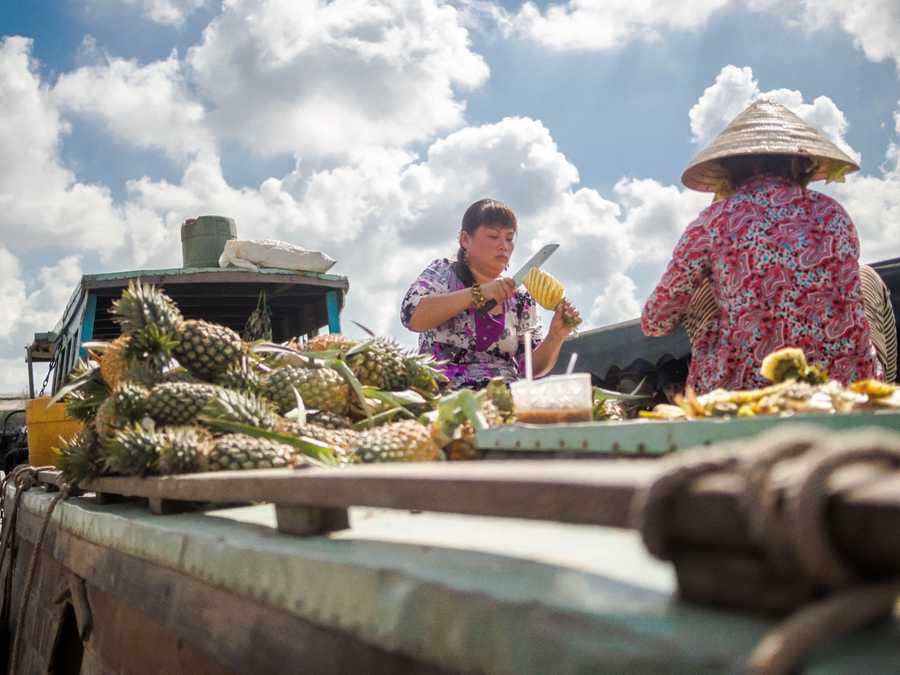 A woman cutting pineapples on the river.