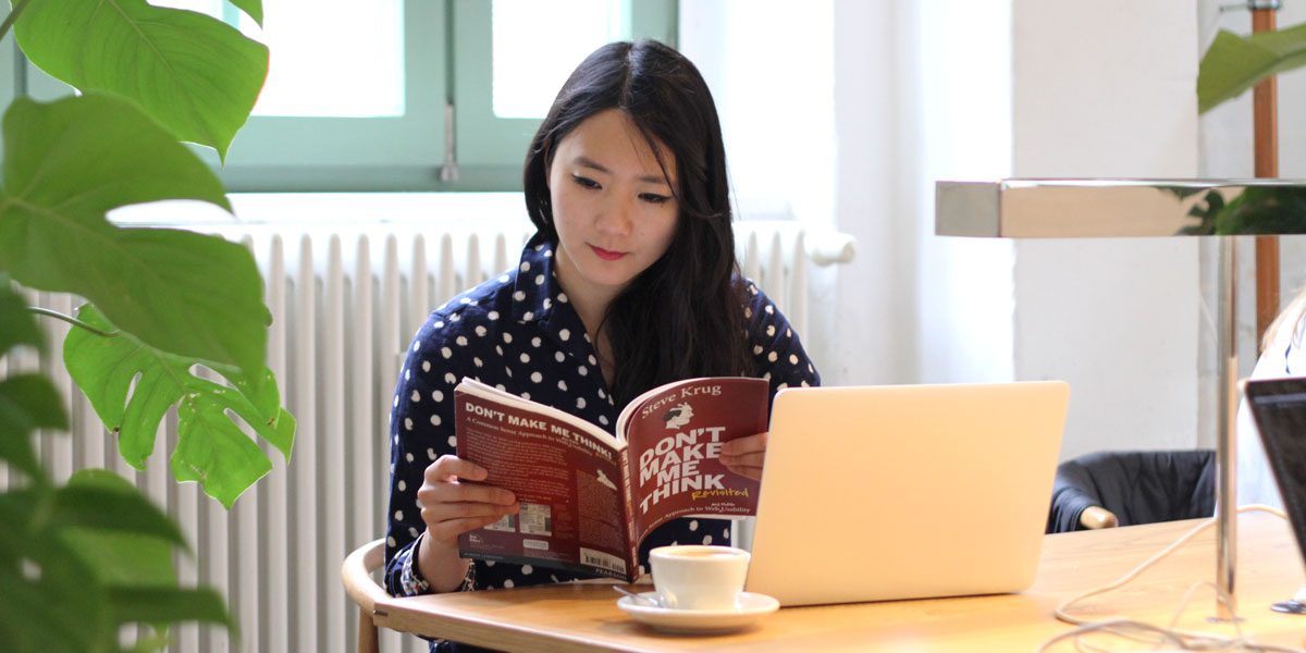 An aspiring UX designer sitting at her desk, reading a book