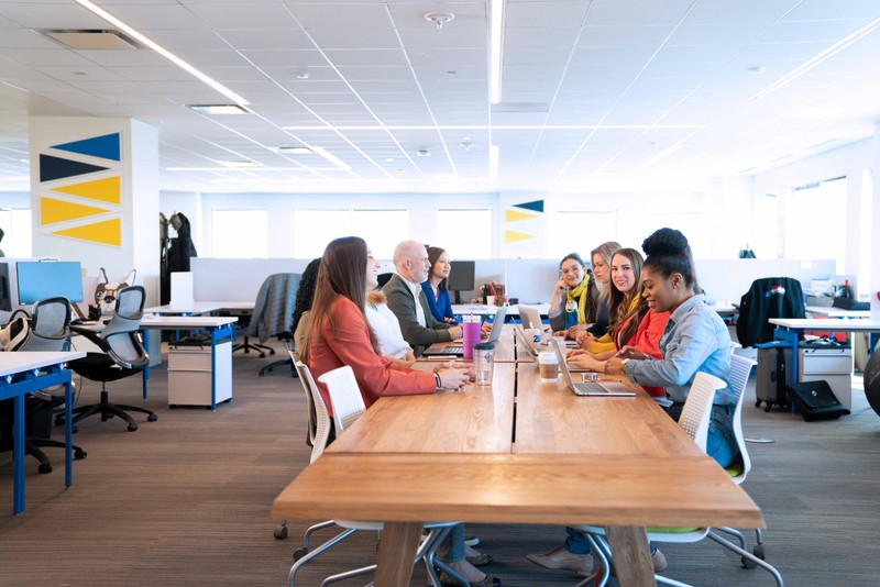 Group of colleagues sitting at a table in their office working on a project