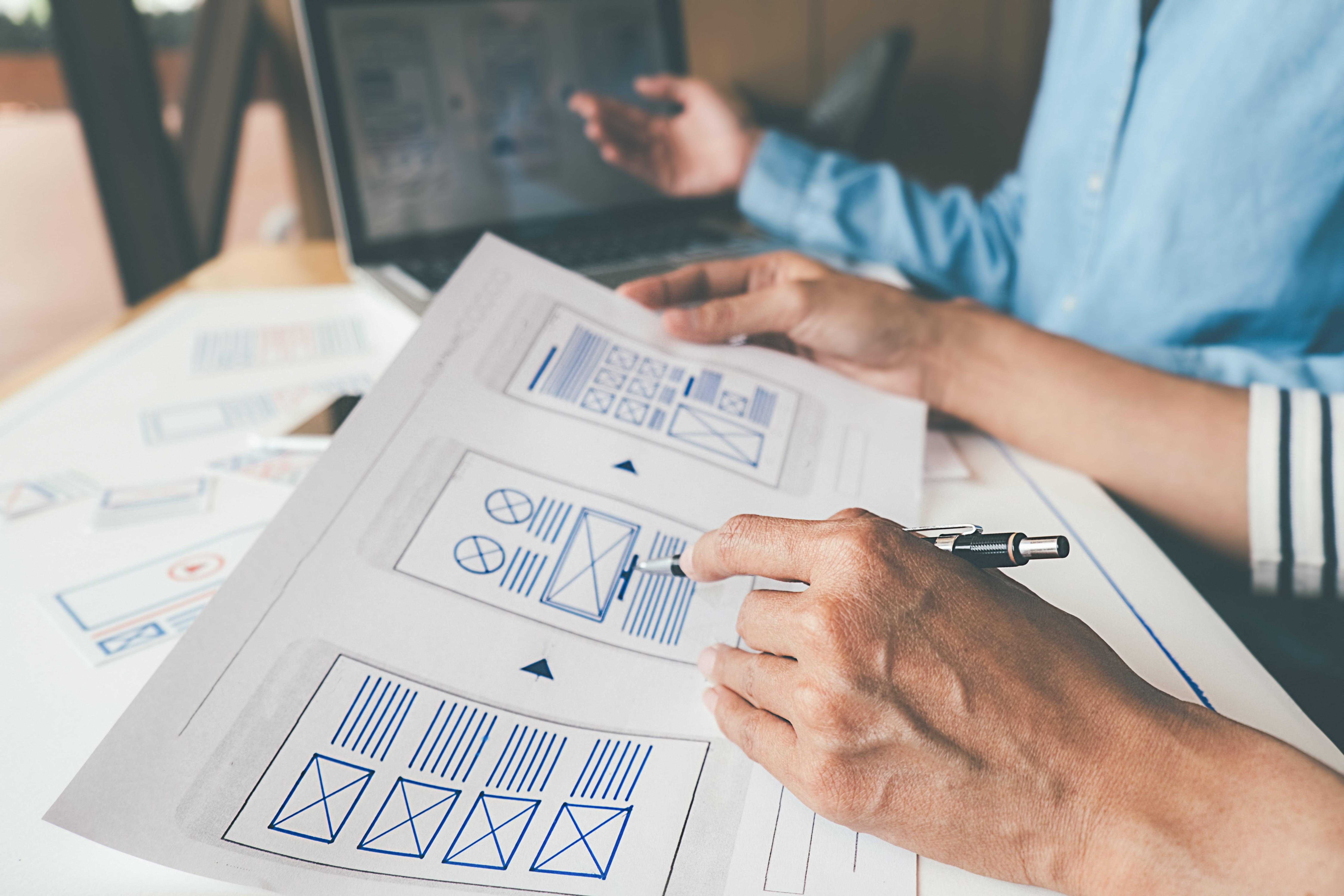 A designer holding some wireframes
