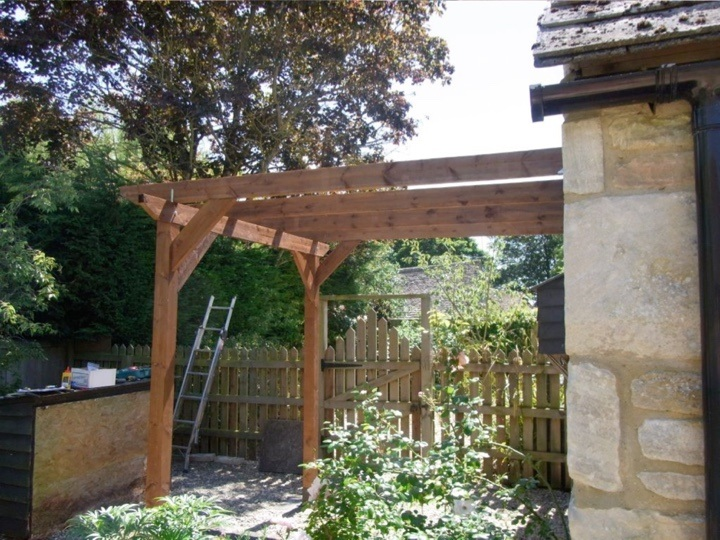 A leon to pergola set against the side of a stone-built house