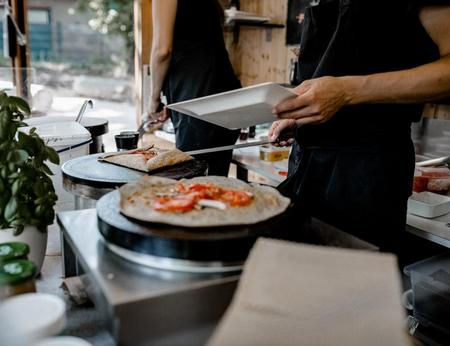 Frische Galette-Zubereitung mit Butter, Gemüse, Käse, Shinken und Spiegelei im rustikalen Food Truck