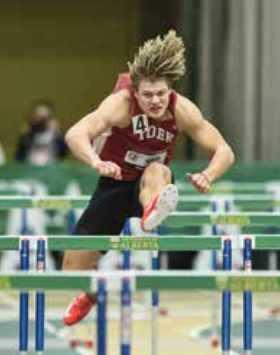 Kayden Johnson jumping hurdles at indoor track field