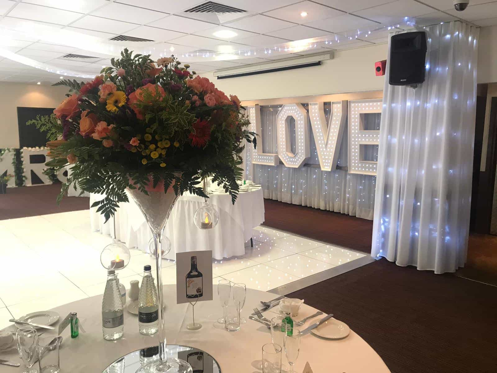 Wedding breakfast dressing with floral and white decor combination. White dancefloor with white silvery backdrop and floral arrangements on the tables