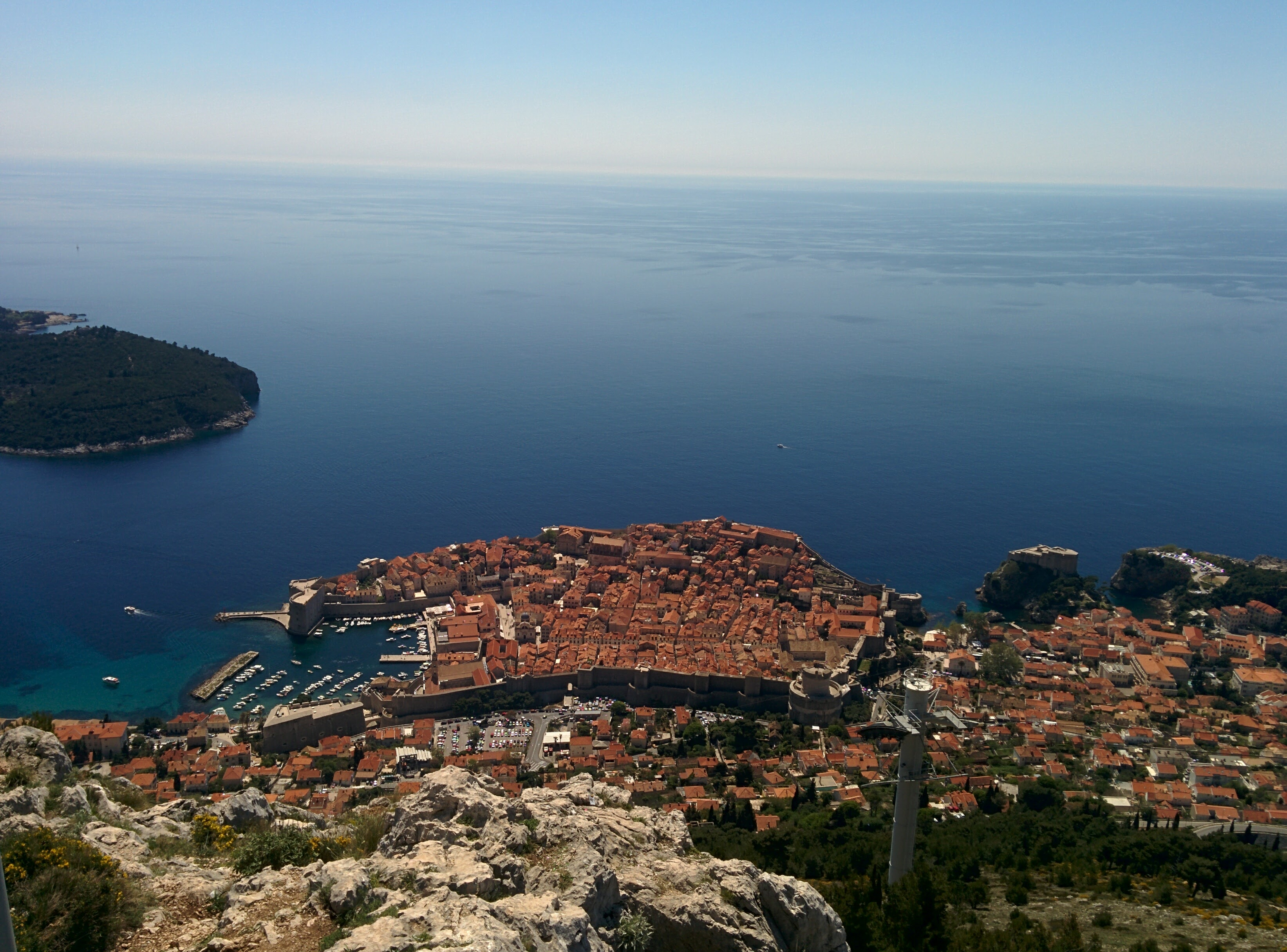 Terracotta rooftops in the Dubrovnik old town viewed from above. Island of Lokrum in the distance.