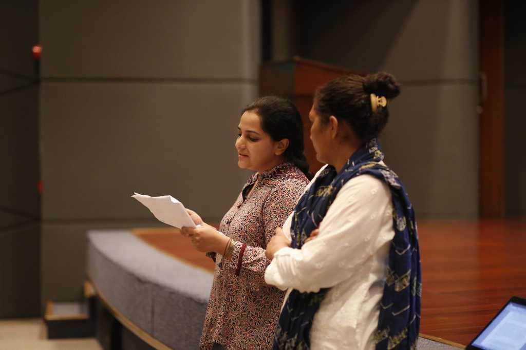 Two women reading script.