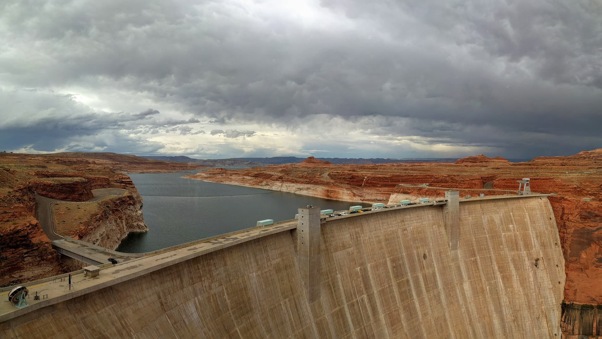 The Glen Canyon Dam, with Lake Powell extending behind it to the horizon. The rocks on either side of the lake are bright red-orange, but turn white just above the water.