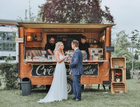 Brautpaar wartet vor schön dekoriertem Crepe-Stand auf die Crepe-Ausgabe
