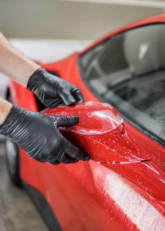 Paint protection film (PPF) being applied to side mirror of Ferrari 458 GTB
