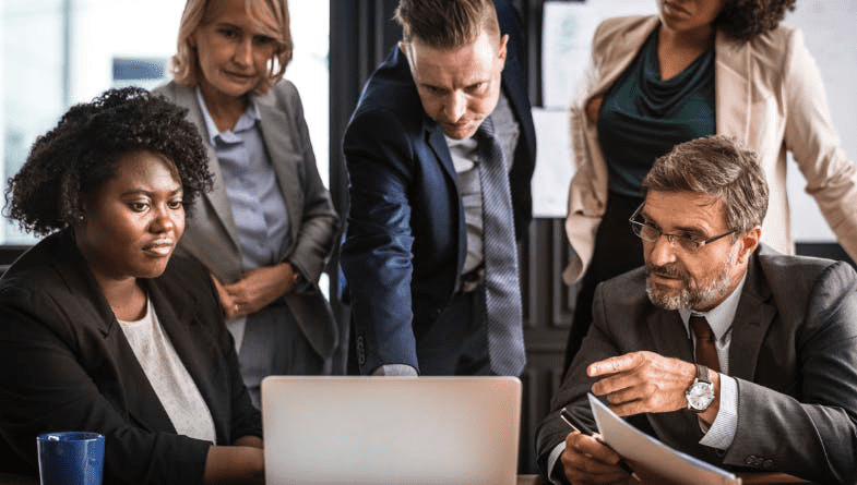 Group of colleagues sit around a laptop and discuss tips to define a target market for marketing a product and brand and business. #business #marketing