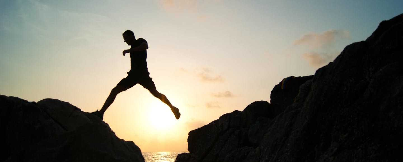 Ein Mann springt von einem Felsen zum anderen - Rentenlücke schließen und Alter genießen