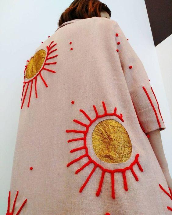 Manteau long rose pâle avec empiècements de tissus et broderies épaisses formant des motifs de soleils
