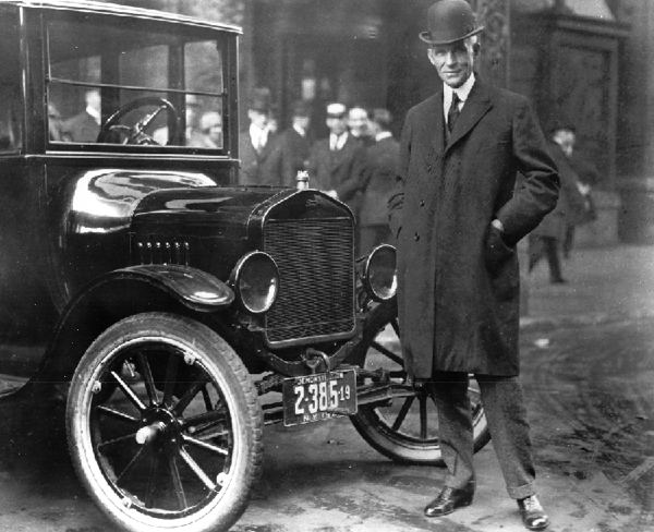 Henry Ford standing by a Ford