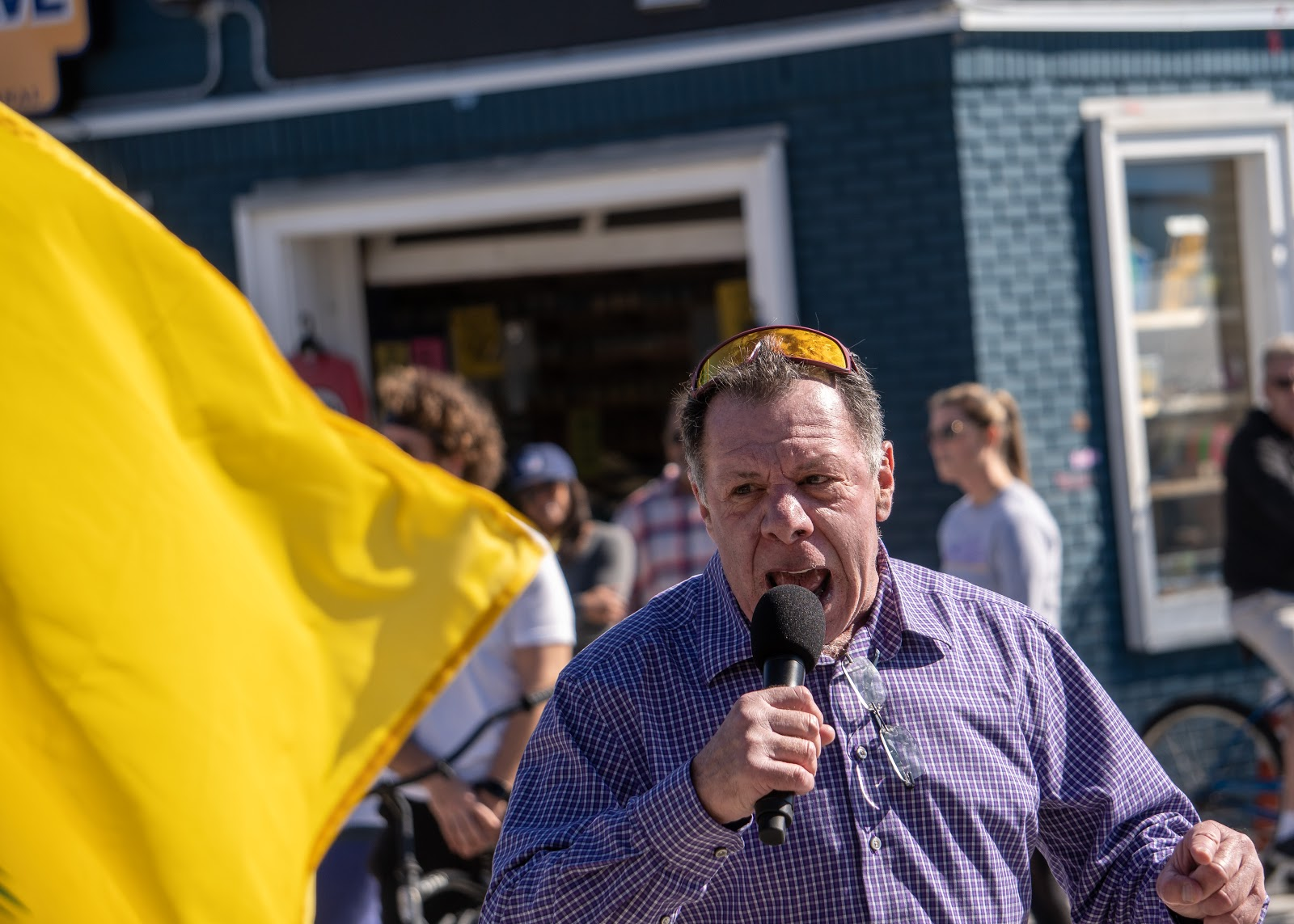 The unidentified speaker yells into a microphone while a gadsden flag blows into frame.N