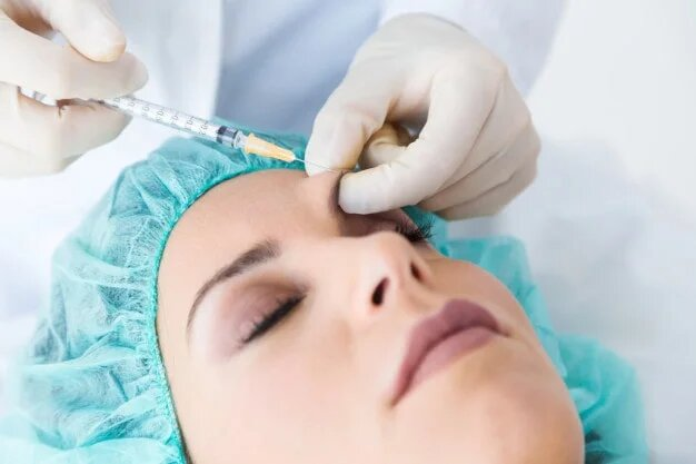 Woman receiving needle injection in her eyebrow section