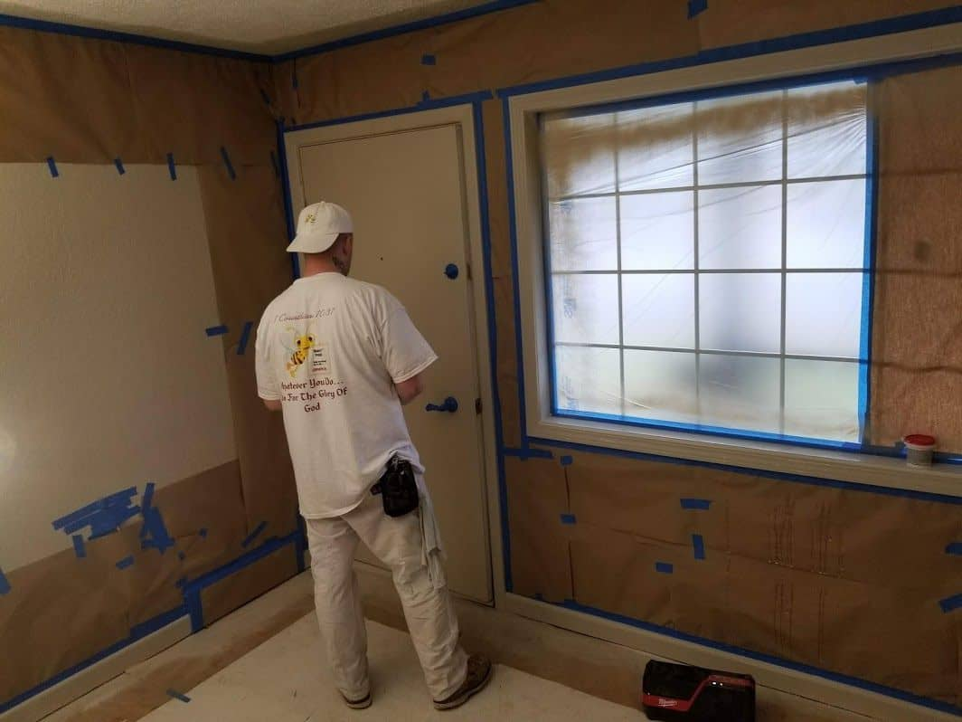 enlarged photo of man taping off a wall