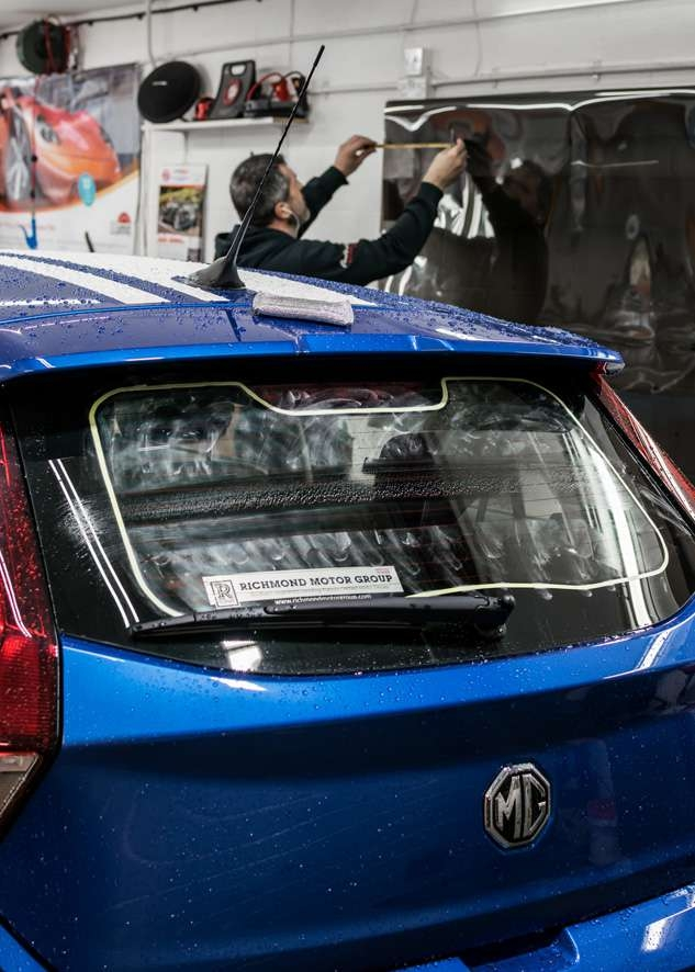 Blue MG3 car rear window being prepared for window tinting