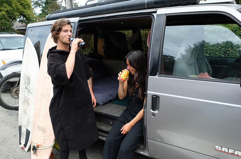 A man taking a sip of Outburst next to Jennifer Yih sitting in a van taking a sip of Blazing Bright