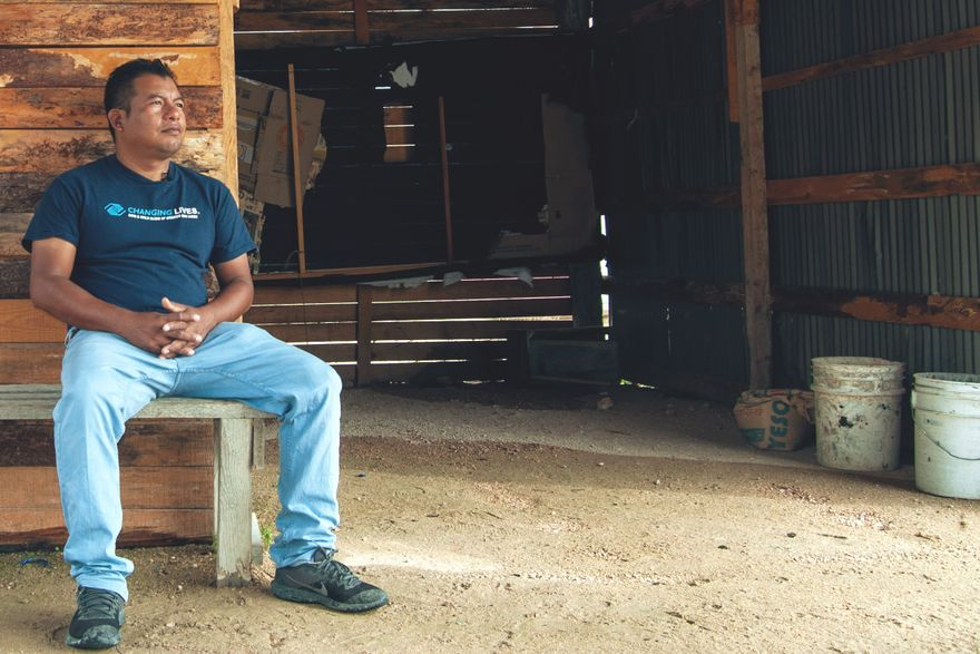 enoc, wearing jeans and a t-shirt, sits on a wooden bench in his garage