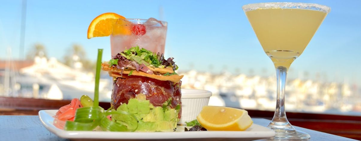Ahi Poke Tower with Avocado, wontons, ginger and wasabi surrounded by two cocktails with the bay in the background