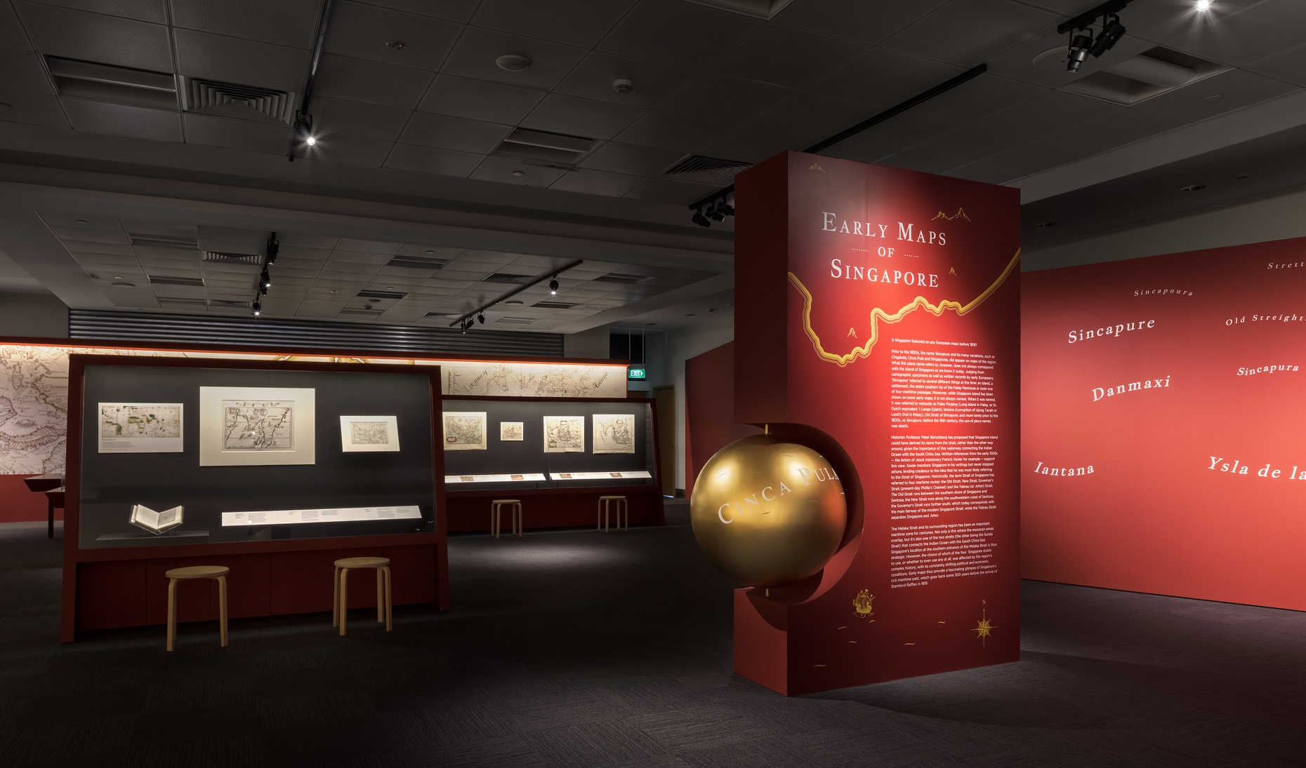 A photo of an exhibition section. The red introduction wall in the middle has a golden globe halfway embedded within it, and its title is Early Maps of Singapore. In the background, several maps are on display. In front of each wall are two chairs and a table showcase.
