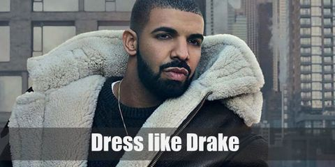 Drake wears a plain black sweater topped with a leather jacket with fur hood, tan pants, a belt, a fashionable pair of sneakers, and a gold necklace.