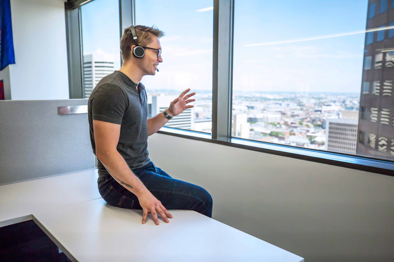 Man in casual clothing speaks on a wireless headset next to a window on an upper floor of an office building